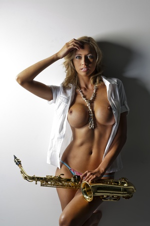 Nude model holding a saxophone against a white background