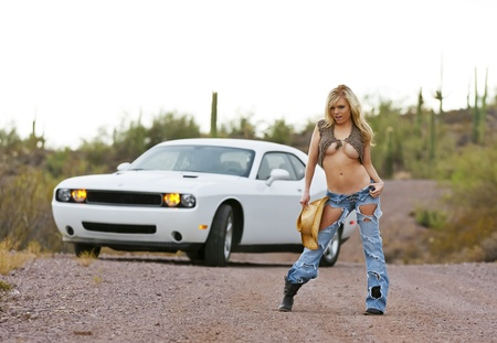 Blonde female model posing with a white car in a desert environment photo