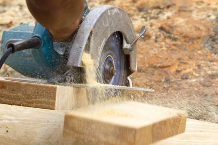 A carpenter cutting wood using a circular saw photo