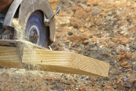 A carpenter cutting wood using a circular saw photo
