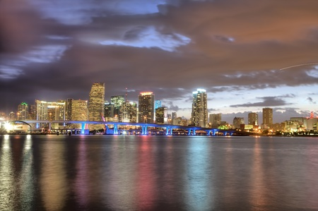 Twilight glow on skyline of Miami along Biscayne Bay on cloudless, calm evening.
