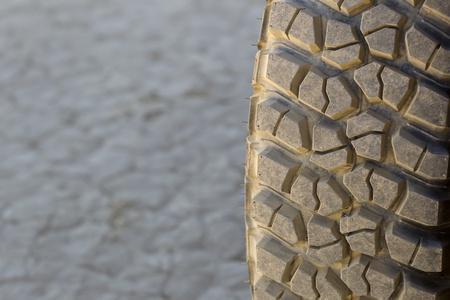 tire: Closeup view of an off road tire tread on a dry lake bed
