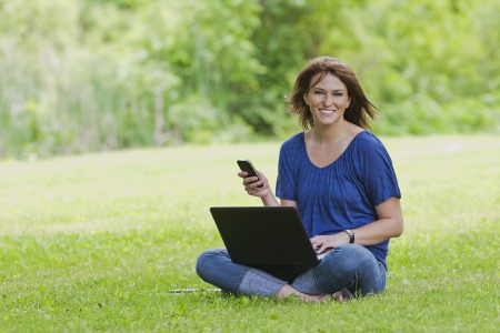 A beautiful brunette model working on a computer and talking on a mobile phone in an outdoor environment photo