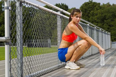 An athletic teenager relaxing after exercising on a track outdoors photo