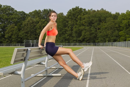 An athletic teenager stretching before exercising on a track outdoors photo