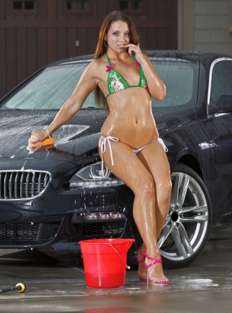 Beautiful bikini models wash a car on a summer day Stock Photo - 14428637
