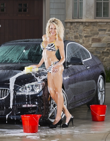 Beautiful bikini models wash a car on a summer day Stock Photo - 14428634