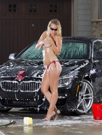 Beautiful bikini models wash a car on a summer day Stock Photo - 14428624