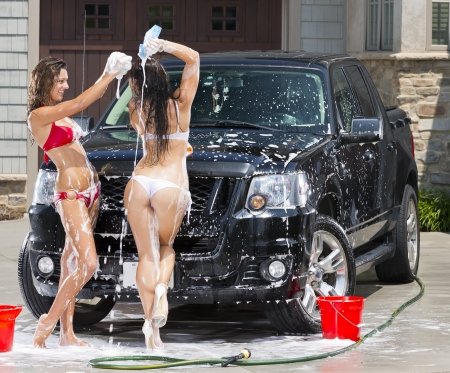 car wash: Beautiful bikini models wash a car on a summer day