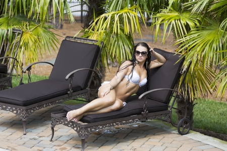 Beautiful bikini model lounges at the pool on a summer day photo