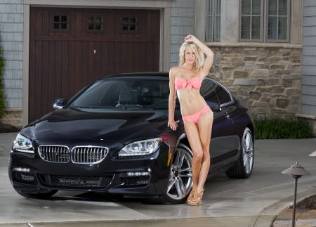 Beautiful bikini models wash a car on a summer day photo
