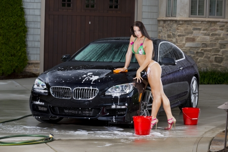 dirty car: Beautiful bikini models wash a car on a summer day