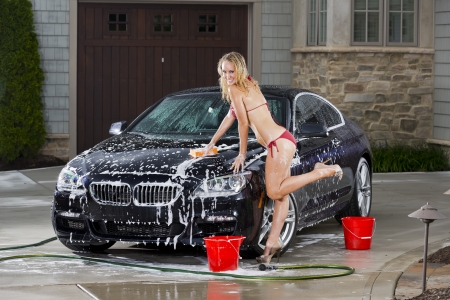 dirty girl: Beautiful bikini models wash a car on a summer day