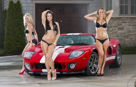 Beautiful bikini models wash a car on a summer day Stock Photo - 14428650