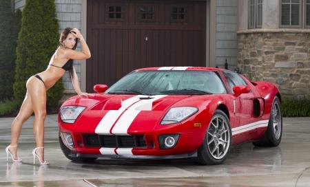 Beautiful bikini models wash a car on a summer day