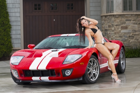 Beautiful bikini models wash a car on a summer day