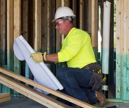 A male construction worker reads blueprints while working at a construction site photo