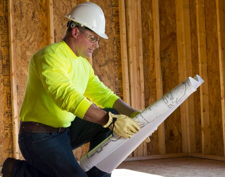 A male construction worker reads blueprints while working at a construction site Stock Photo - 14531939