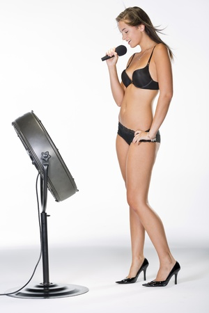Brunette model singing in lingerie in a studio environment photo