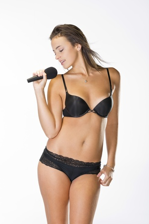 bra model: Brunette model singing in lingerie in a studio environment