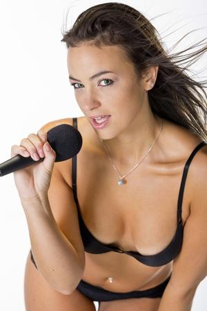 Brunette model singing in lingerie in a studio environment photo