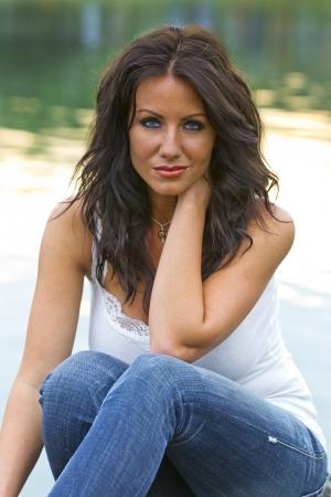 Brunette model sitting in a park near a pond