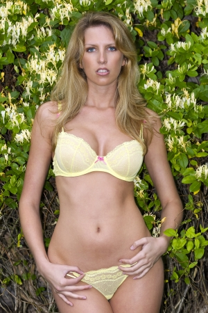 A blonde model in yellow lingerie with flowers around her in an outodoor environment photo