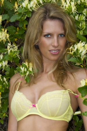 A blonde model in yellow lingerie with flowers around her in an outodoor environment Stock Photo - 14826290