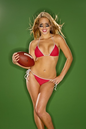 A blonde model posing with a football in a studio environment photo