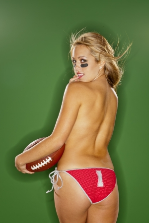 sexy bikini girl: A blonde model posing with a football in a studio environment Stock Photo