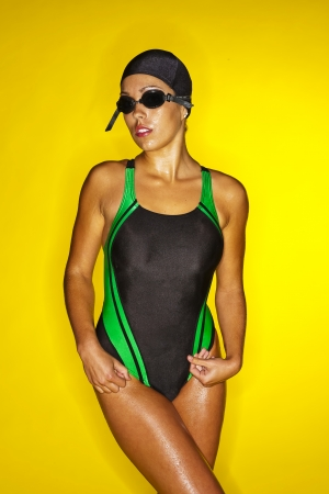 A female swimmer poses in a studio against a yellow background Stok Fotoğraf