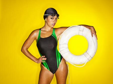 A female swimmer poses in a studio against a yellow background Stock Photo