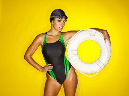 A female swimmer poses in a studio against a yellow background Archivio Fotografico