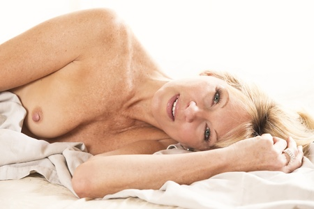 A sexy seductive mature model posing nude in bed
