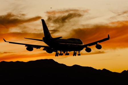 Commercial aircraft land at an airport at sunset photo