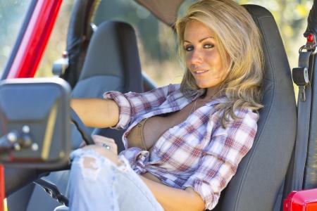 필드에 자동차와 함께 아름 다운 금발 모델 포즈 스톡 콘텐츠