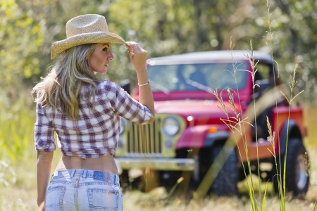 Beautiful blonde model posing with a car in a field photo