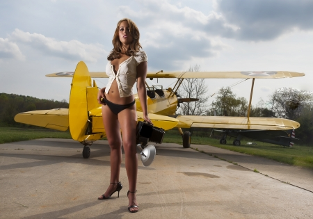 biplane: Brunette model posing with a WW1 aircraft