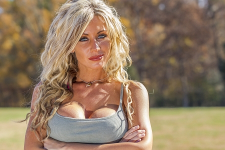 A blonde model posing outdoors at a park