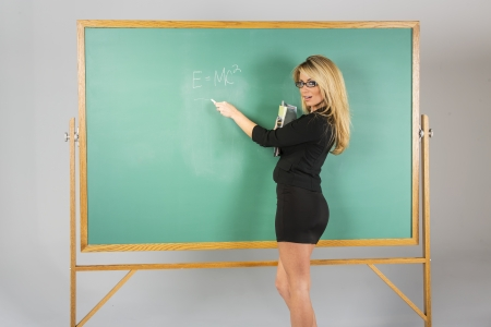 An attractive school teacher in front of a chalkboard    Imagens
