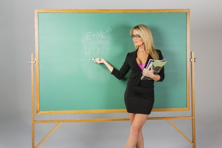 An attractive school teacher in front of a chalkboard    Stock Photo - 18055586