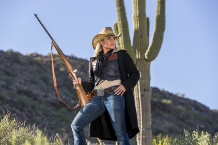 A blonde model posing as a cowgirl in a western environment