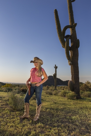A blonde model posing as a cowgirl in a western environment photo