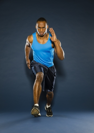 A young black athlete running against a dark background photo