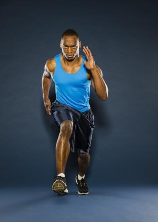 Een jonge zwarte atleet die tegen een donkere achtergrond Stockfoto