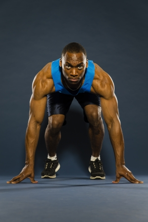 A young black athlete running against a dark background