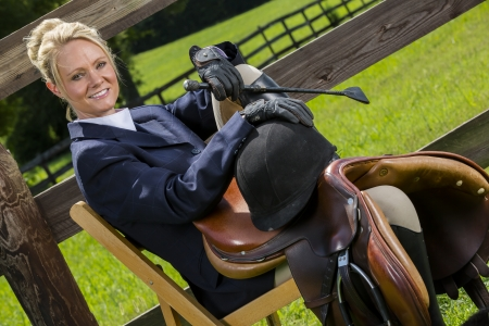 A blonde equestrian model poses in an outdoor environment