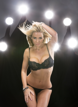 A blonde attractive lingerie model poses in a studio environment with lights in the background  photo