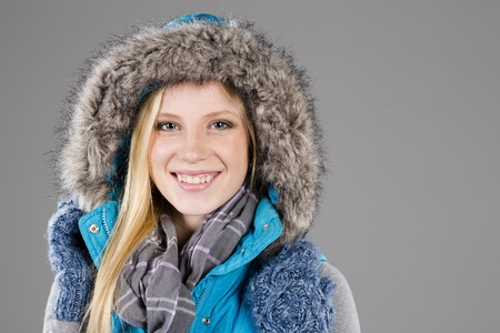 A blonde model poses in a studio environment wearing winter clothing photo