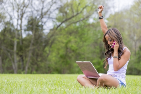 A young female african-american woman working on her laptop computer, enjoying a day at the park